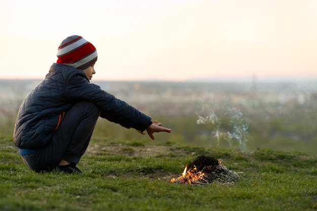 Child boy warming near bonfire outdoors in cold weather.
