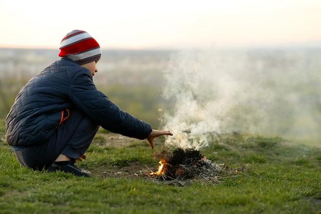 Ребенок мальчик потепления возле костра на улице в холодную погоду