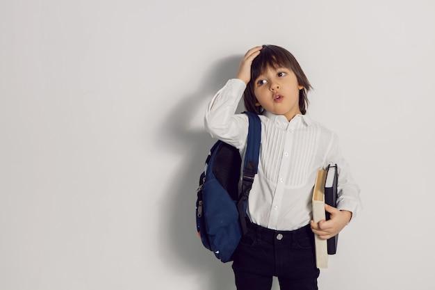 Ребенок мальчик с книжным учебником и рюкзаком стоит на белой стене