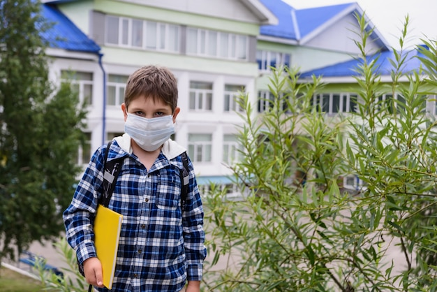 Ребенок мальчик с сумкой, маской и книгой остается возле начальной школы