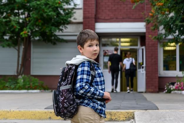Мальчик с сумкой стоит возле начальной школы и смотрит на камеру