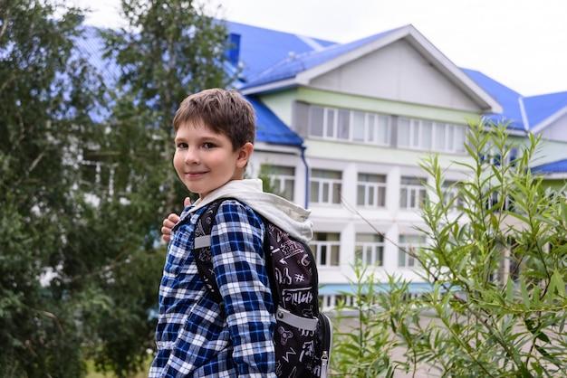 Ребенок мальчик с сумкой остается возле начальной школы