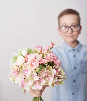 Child boy with bouquet of flowers. mother's day greeting card. happy mothers day frame background.