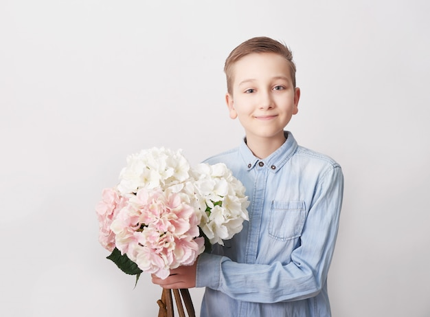 Child boy with bouquet of flowers. mother's day