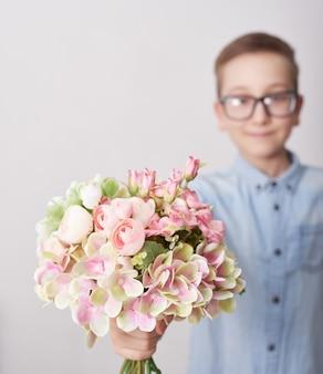 花の花束を持つ子少年。母の日グリーティングカード。幸せな母の日フレームの背景。