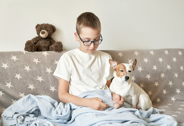 Child boy with dog jack russell terrier sitting on the couch, the boy has a cold