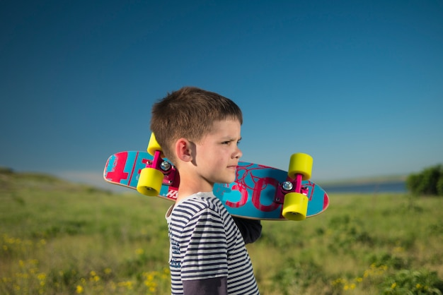 Child boy with skateboard in nature
