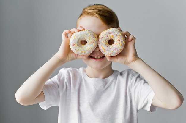 Child boy with white donuts against grey background. funny time with food.