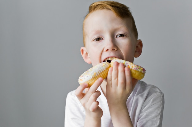 Child boy with white donuts against grey background.
