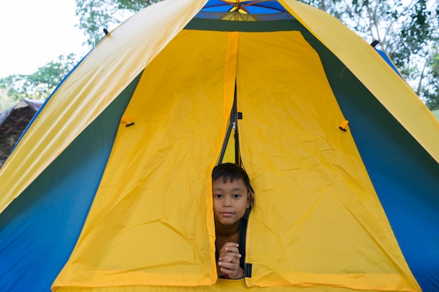 Child boys are in the tent during camping.