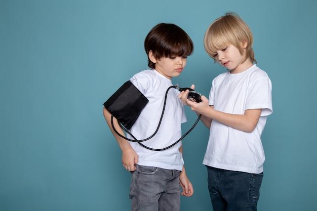 Piccola pressione di misurazione adorabile sveglia dei ragazzi del bambino in magliette e jeans bianchi