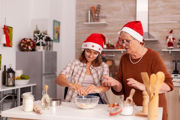 自家製の伝統的なクッキー生地を作るボウルで卵を割る子供