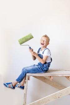 Ребенок строитель сидит на строительной лестнице в квартире и держит сруб для покраски стен
