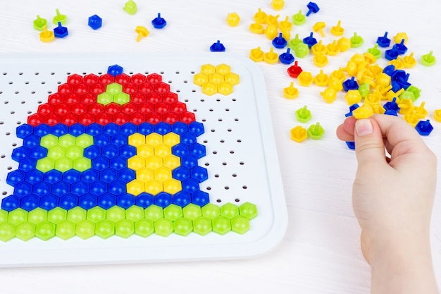 Child building a mosaic house