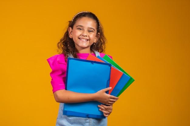 育児と幸せな子供時代、学校での初日の準備ができている本を持つかわいい女の子。