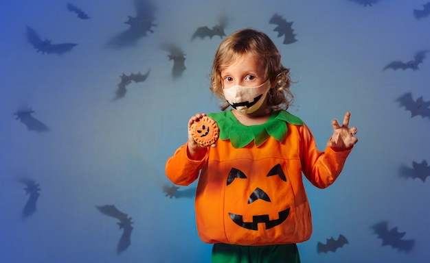 Child in carnival costume playing with cookies and at halloween party