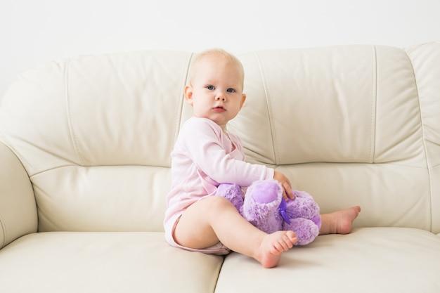 子供、子供時代、子供たちのコンセプト-ソファの上の魅力的な女の赤ちゃんの肖像画