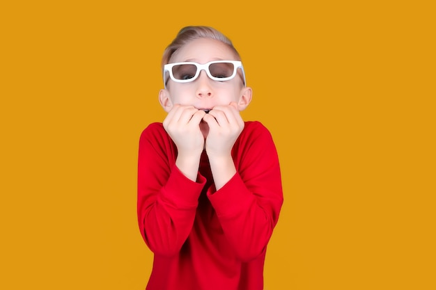 A child in children's 3d glasses bites his nails in surprise