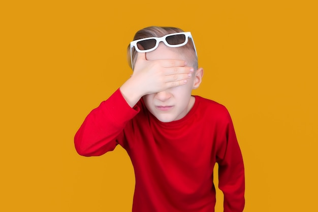 A child in children's 3d glasses covered his eyes with his hand