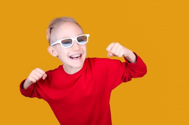 A child in children's 3d glasses joyfully raises his hands
