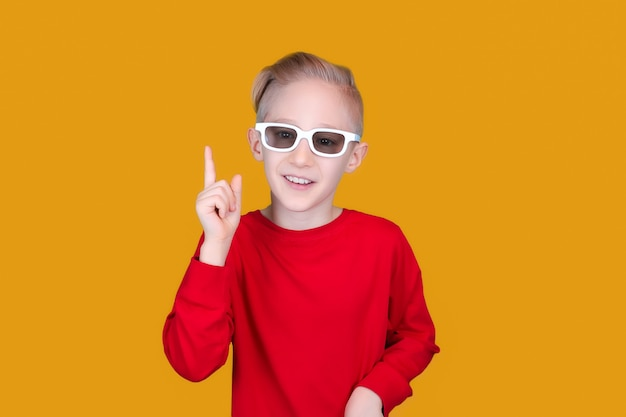 A child in children's 3d glasses raised his finger up on a yellow background