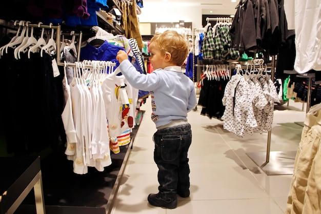 Ребенок выбирает одежду в продаже модного магазина