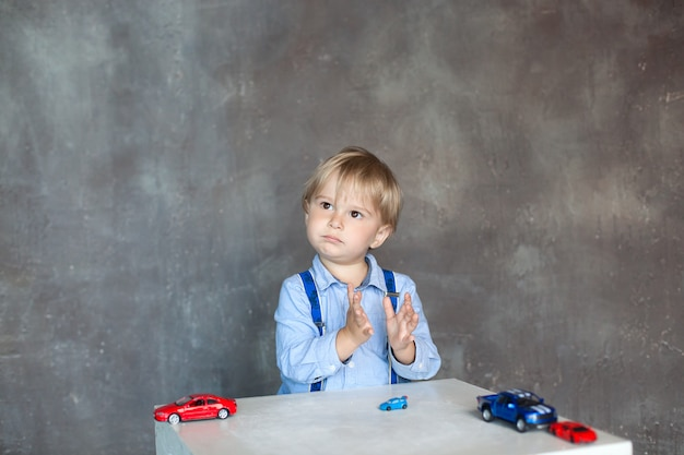 The child claps his hands. portrait of a cute little boy playing with cars. preschool boy playing with toy cars in kindergarten. educational toys for preschool and kindergarten children.
