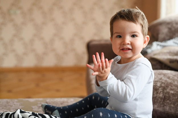 Child claps while sitting at home