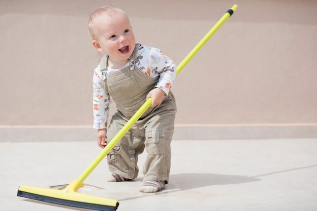 床を掃除する子供。かわいい男の子が家の掃除をします。少年は床を拭きます。