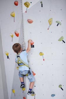 Ребенок, взбирающийся на высокую стену