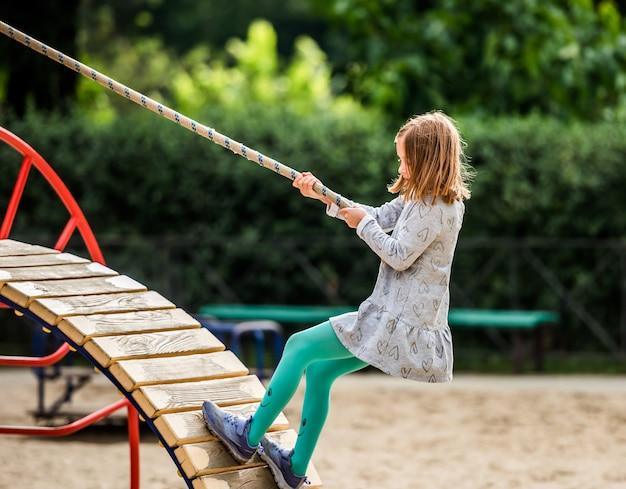 晴れた日に屋外のスポーツ遊び場にロープで登る子