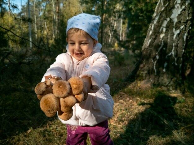 Ребенок собирает опята в осеннем лесу малыш держит красивые съедобные грибы