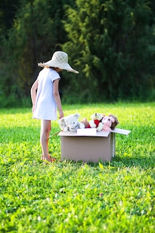 Ребенок собирает игрушки на благотворительность. мягкие игрушки в картонной упаковке на природе.