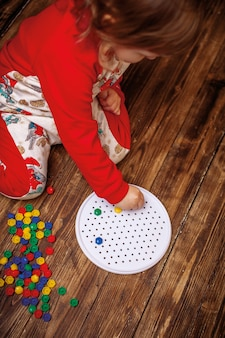Child collects the picture from the mosaic. development of motor skills