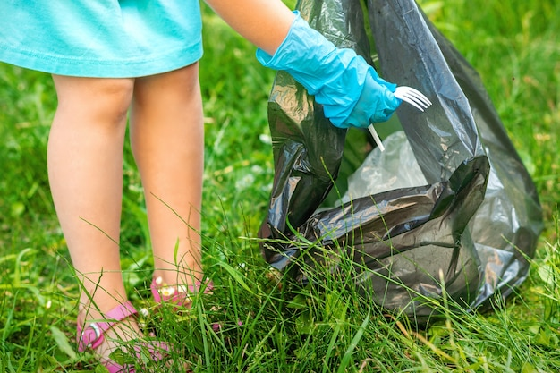 Child collects plastic trash from grass throwing garbage in garbage bag in the park