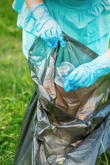 Ребенок собирает пластиковый мусор с травы, выбрасывая мусор в мешок для мусора в парке