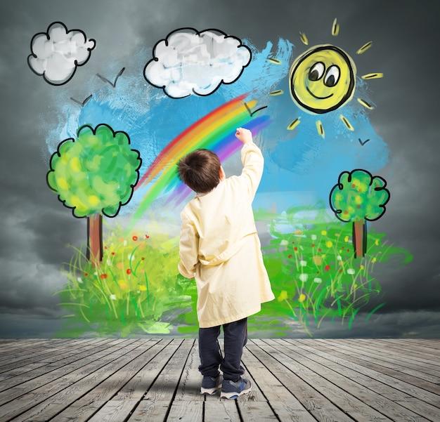 Ребенок раскрашивает солнечный пейзаж на серой стене с облаком