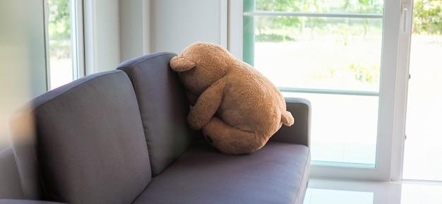 Детская концепция скорби. сидит плюшевый мишка, прислонившись к стене дома, выглядит грустным и разочарованным.