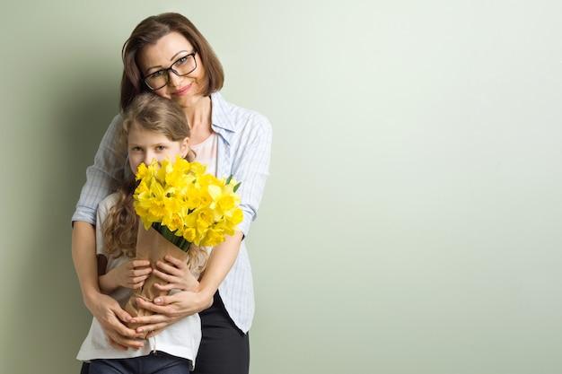 子供は母親を祝福し、彼女の花束を与えます