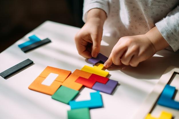Ребенок соединяет кусочки разноцветной деревянной головоломки.