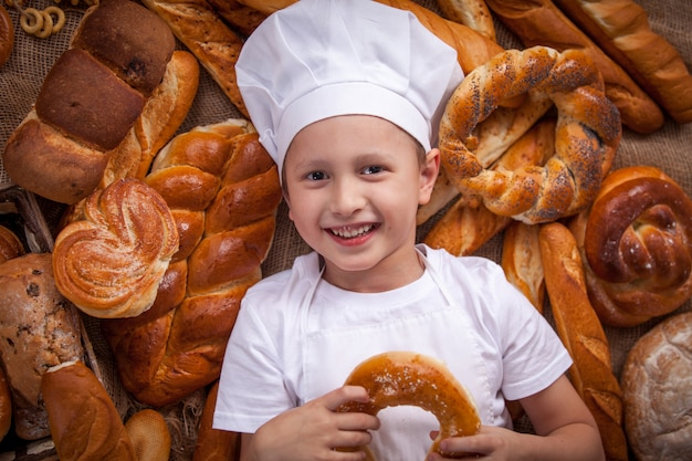 Child cook dressed up lies baker a lot of bread rolls