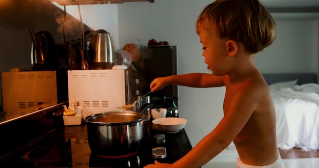Child cooks himself pasta in the kitchen in the morning