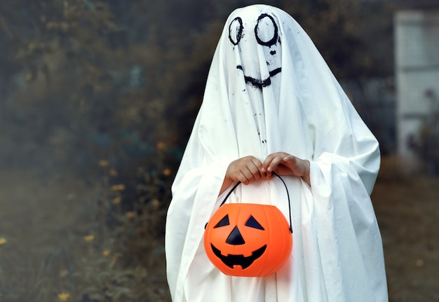 Child in costume ghost with pumpkin in forest halloween celebration holiday funny smiling grimace