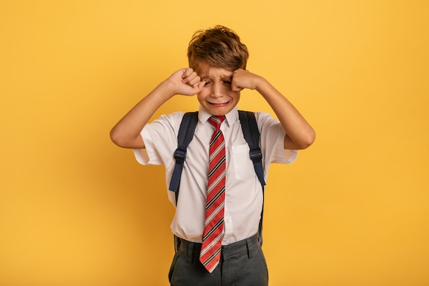 Child cries because does not want to go to school. yellow background