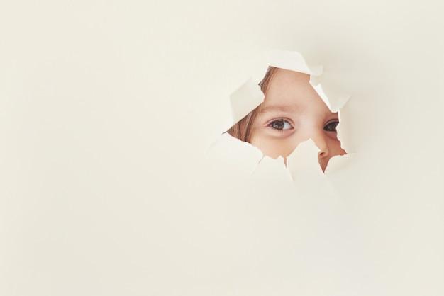 子供の好奇心。小さな女の子の目が透けて見える白い紙の破れた穴。