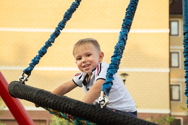 Child, cute caucasian boy riding swing on playground near his house in a town