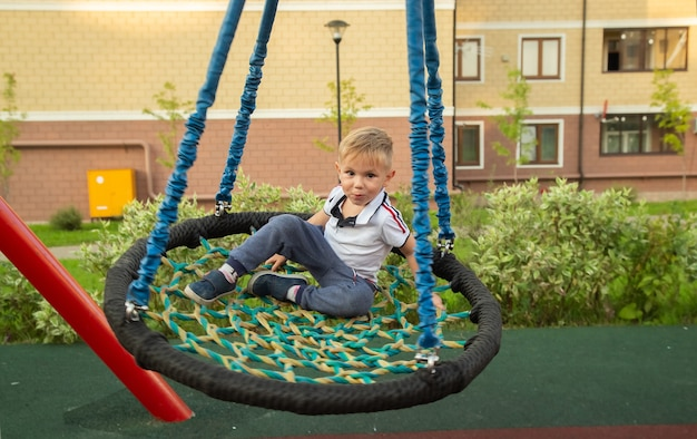 Child cute caucasian boy riding swing on playground near in a town