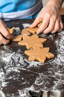 Child cutting out cookies from dough at home kitchen