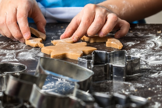 Child cutting out cookies from dough at home kitchen.