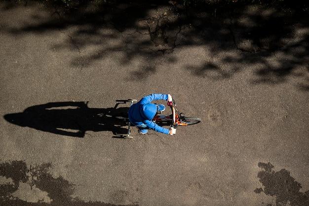 ロードトップビューの都市シーンで子供サイクリング